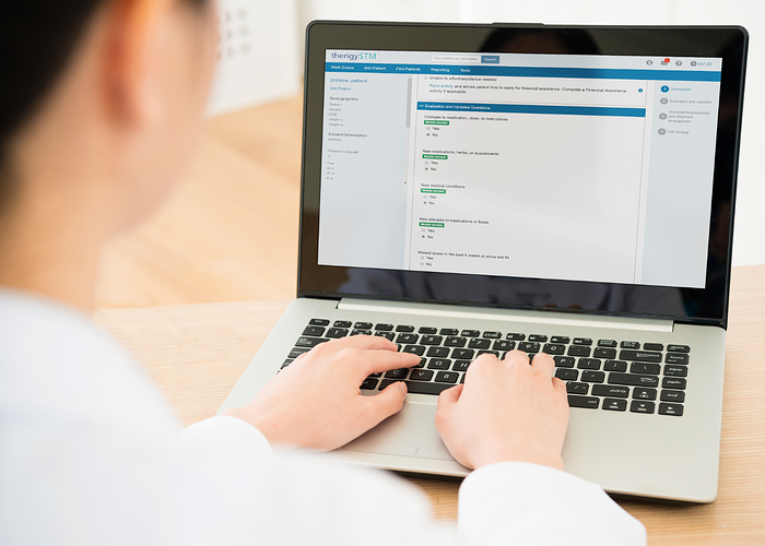 A pharmacist using TherigySTM to check patient answers from Mobile Assessments.
